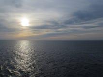 Coucher du soleil nuageux dans l'océan Photos stock