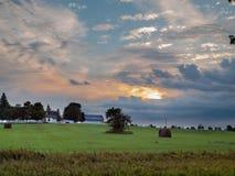 Coucher du soleil nuageux de Colorfull au-dessus de maison rurale de ferme Photos stock