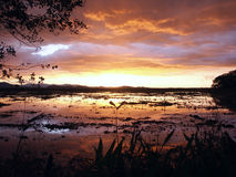 Coucher du soleil orageux au-dessus de lac photo stock