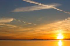 Coucher du soleil orange au-dessus d'océan et de montagnes Images stock