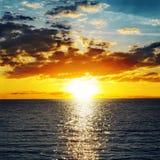 Coucher du soleil orange au-dessus de l'eau Image stock
