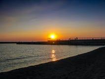 Coucher du soleil orange au-dessus de la baie et du mail image stock