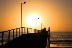 Coucher du soleil orange derrière la jetée de plage Photo stock