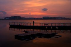 Coucher du soleil orange 2 - pêche d'homme sur la plate-forme photos libres de droits
