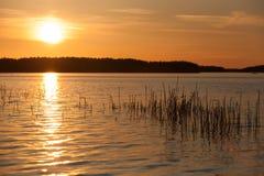 Coucher du soleil orange sur le lac en Finlande Images stock