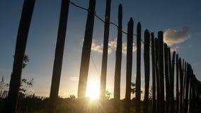 Coucher du soleil par la barrière Image libre de droits