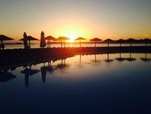 Coucher du soleil par la piscine images libres de droits