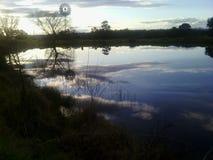 Coucher du soleil par le barrage Photo libre de droits