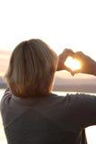 Coucher du soleil par les mains en forme de coeur Photographie stock libre de droits