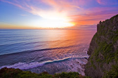 Coucher du soleil par une falaise Photographie stock libre de droits