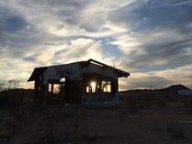 Coucher du soleil par une maison abandonnée Photo libre de droits