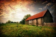 Coucher du soleil par une vieille grange photo libre de droits