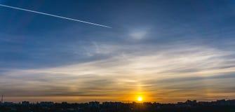 Coucher du soleil pittoresque au-dessus de la ville et d'une voie d'un avion de départ dans le ciel Photos libres de droits