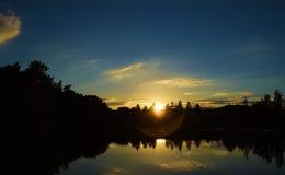 Coucher du soleil près de petite ville Okrisky près d'étang Photo libre de droits