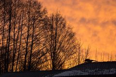 Coucher du soleil romantique avec une partie du toit d'une maison Photographie stock libre de droits