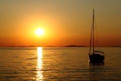 Coucher du soleil romantique d'or avec le yacht photographie stock libre de droits
