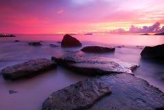Coucher du soleil rosâtre et la roche à la côte Image libre de droits