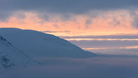 Coucher du soleil rose et orange en montagnes couvertes de neige Photographie stock libre de droits