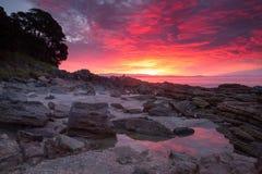 Coucher du soleil rouge ardent au-dessus d'une côte rocheuse image libre de droits