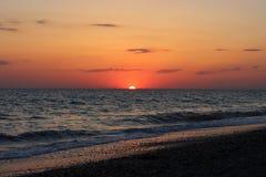 Coucher du soleil rouge ardent au-dessus de la mer Photo stock