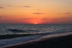 Coucher du soleil rouge ardent au-dessus de la mer Photographie stock