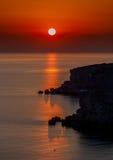 Coucher du soleil rouge au-dessus de l'eau Images stock