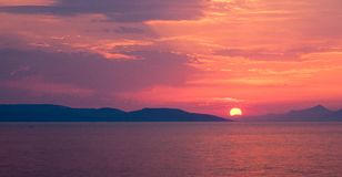 Coucher du soleil rouge au-dessus de la mer avec le soleil entre les collines, panorama Image stock