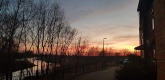Coucher du soleil rouge au-dessus de rivi?re avec des nuages de gradient de couleur image libre de droits
