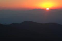 Coucher du soleil rouge au-dessus des montagnes fumeuses Photographie stock libre de droits