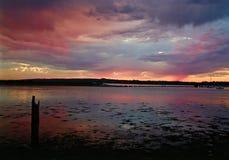 Coucher du soleil rouge avec des nuages de pluie au-dessus de l'eau et de terre dans la distance Photos stock