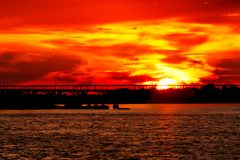 Coucher du soleil rouge avec la silhouette du pont photos libres de droits