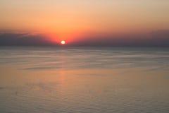 Coucher du soleil rouge contre la mer bleue avec des vagues Photographie stock libre de droits