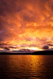 Coucher du soleil rouge du feu dramatique au-dessus d'un lac Image stock