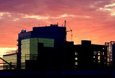 Coucher du soleil rouge-foncé d'été au-dessus d'un chantier de construction Photo stock