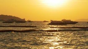 Coucher du soleil rouge sur la mer avec des bateaux balançant sur les vagues thailand Pattaya banque de vidéos