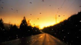 Coucher du soleil rougeoyant concentré sur des gouttes de pluie Photographie stock libre de droits