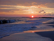 Coucher du soleil rougeoyant sur la plage Image stock