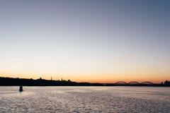 Coucher du soleil saisissant au-dessus du lac avec les nuages et le ciel lumineux Images stock