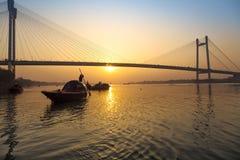 Coucher du soleil scénique au-dessus de pont de Vidyasagar avec les bateaux en bois sur la rivière Hooghly, Kolkata, Inde photos libres de droits