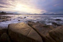 Coucher du soleil se reflétant outre de l'océan et des roches Photographie stock