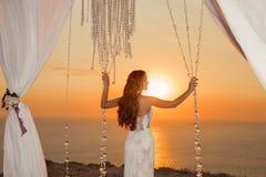 Coucher du soleil Silhouette de jeune mariée Voûte de cérémonie de mariage avec le curta blanc Photos libres de droits