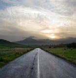 Coucher du soleil sombre sur la route vide photo stock