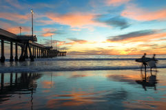 Coucher du soleil spectaculaire avec des surfers à la plage de Venise Image stock
