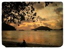 Coucher du soleil sur l'océan, silhouettes. Vieille carte postale Photo stock