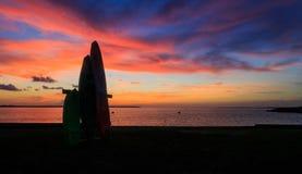 Coucher du soleil sur la baie avec des canoës et des kayaks comme silhouettes en été photographie stock