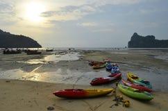 Coucher du soleil sur la baie de Loh Dalum avec des bateaux et des kayaks de longue queue à marée basse Photographie stock libre de droits