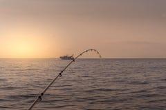 Coucher du soleil sur la mer avec une canne à pêche dans le plan rapproché et un b de pêche Photos stock