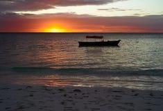 Coucher du soleil sur la plage avec la silhouette d'une petite pêche image libre de droits