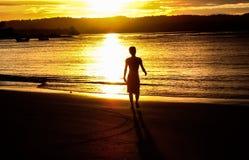 Coucher du soleil sur la plage avec une silhouette Images stock