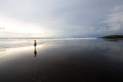 Coucher du soleil sur la plage noire de sable Image stock